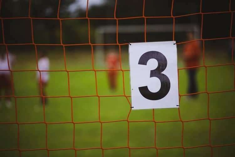 A sign showing the number 3 attached on the net of a goalpost.