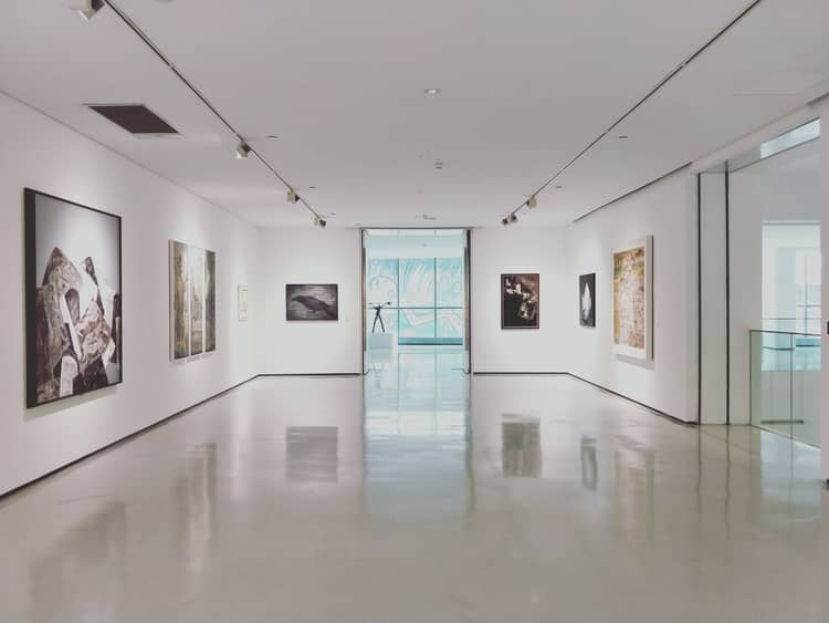 An art gallery with several paintings mounted against its white walls. Emphasizing the importance of having white spaces between the paintings.