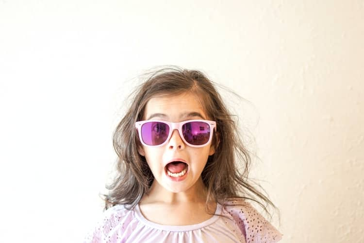 A girl wearing pink sunglasses with her mouth opened wide.