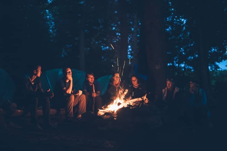 A group of people sitting by a bonfire and telling stories.