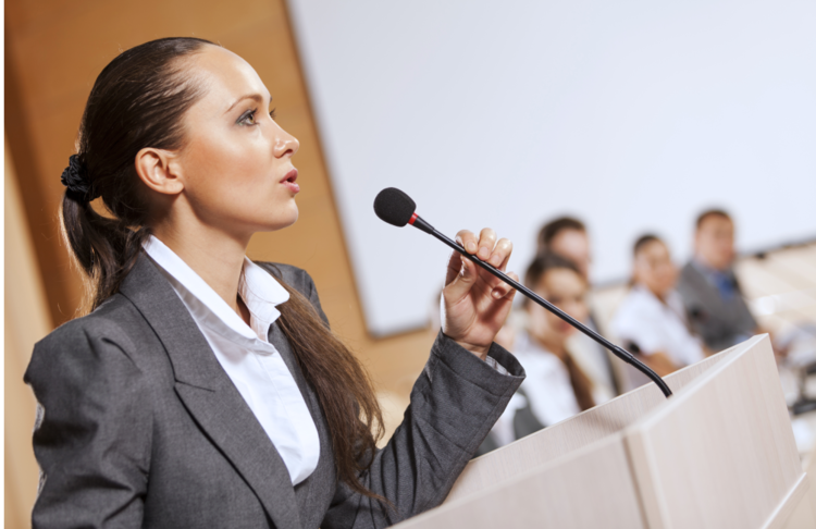 A female professional speaking into a mic with an open body language.