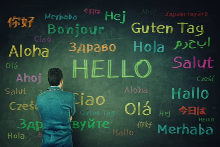 Man looking at a board with various languages which he may be learning and not able to speak fast in.