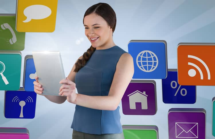Woman wearing a blue shirt smiling at a grey tablet with symbols of communication apps in the background.