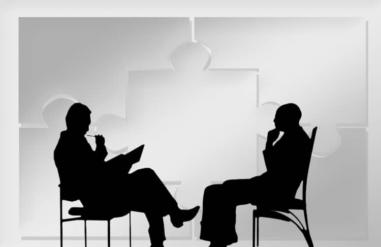 Outlines of two businessmen sitting opposite each other and conversing against a grey colored puzzle background.