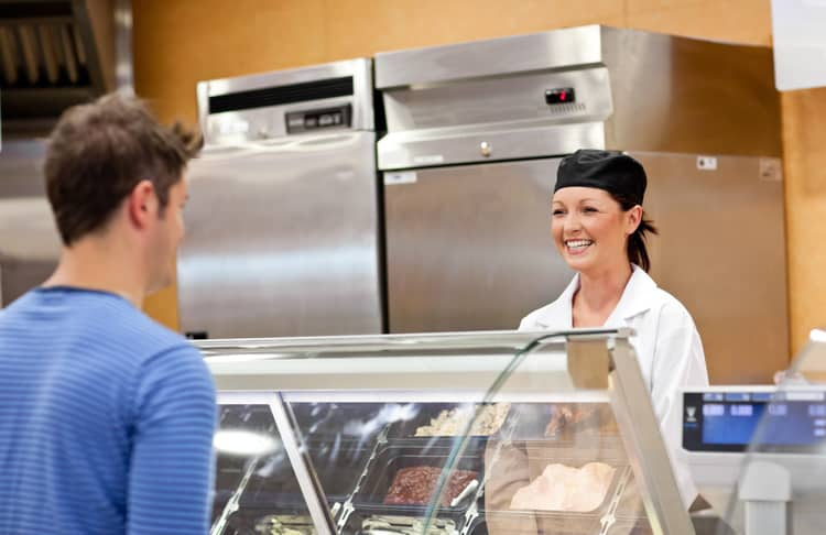 A working woman standing behind a service counter smiling at a man wearing a blue striped shirt