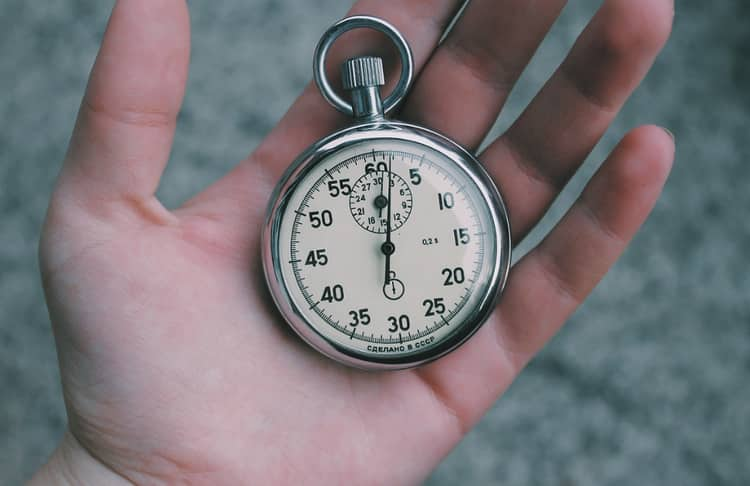 Hand holding a pocket watch showing the importance of time management.