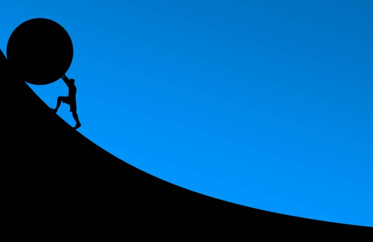 silhouette of a man pushing a boulder up a hill and facing his obstacles.