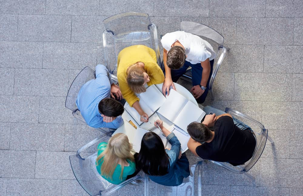 Group of students sitting around a table and studying