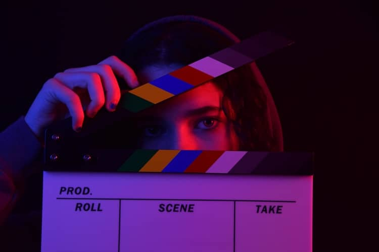 a girl holding a clapperboard signifying action.