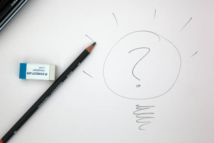 a white paper with a pencil and an eraser kept on it and a question mark drawn, suggesting an idea.