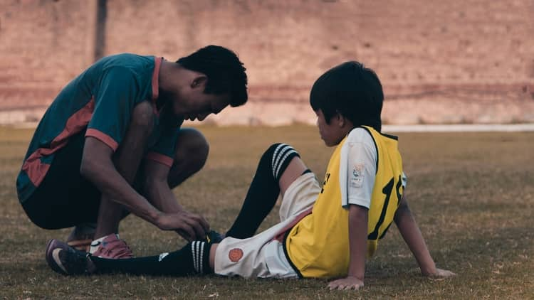 a coach tying his team member's shoelaces.