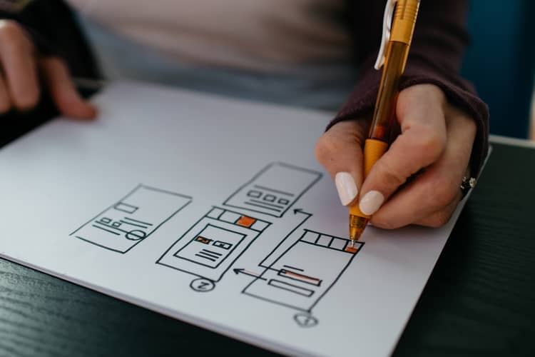 a person drawing an outline on a blank page.