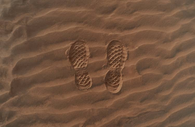 Prints of a pair of shoes on sand.