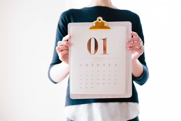 a woman holding a calendar with the month of January on the cover page.
