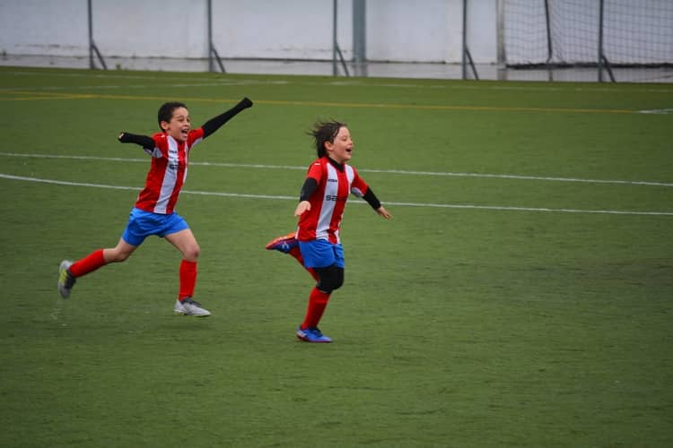 two young footballers running and celebrating victory.