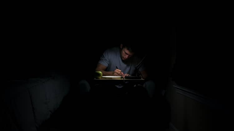 a person seated at a desk, writing something in a notebook in a dark room.