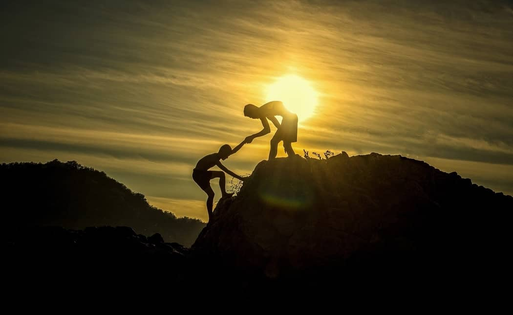 silhouettes of two people climbing a mountain peak. One person helping the other.